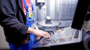 Mitarbeiter an bedient eine CNC-Fräse